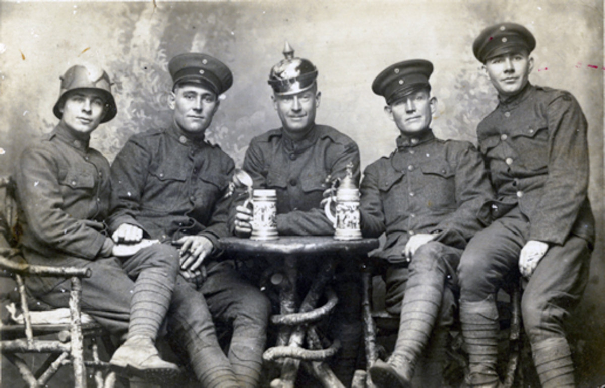 Are the days numbered for soldiers bringing home trophies —like this group of WWI American soldiers all wearing some form of German headgear? Several laws in place seem to indicate it is possible. (Real photo postcard courtesy of Brennan Gauthier)
