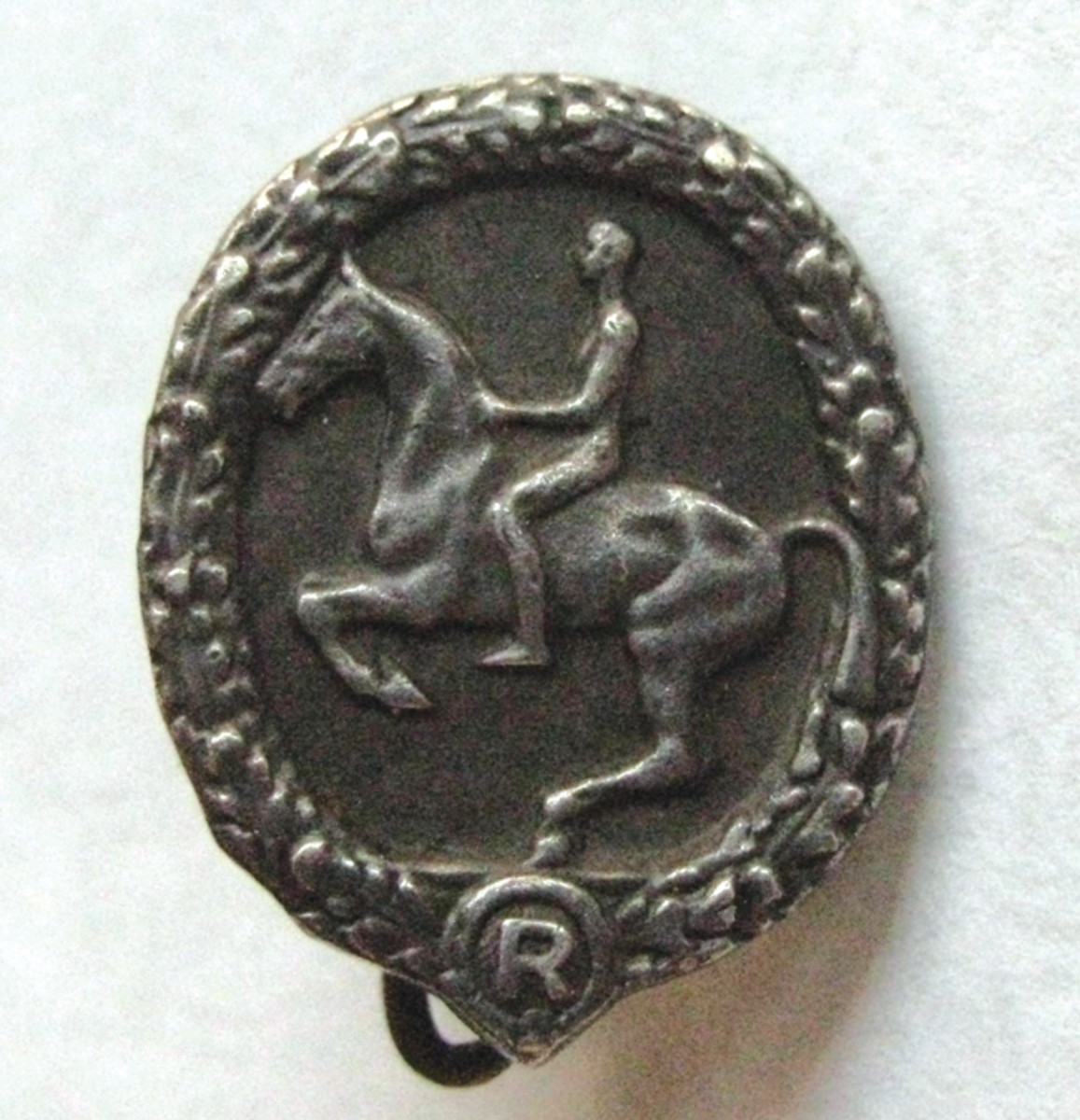 This silver miniature Horseman's Badge is in a pin back configuration rather than the more common stick pin attachment.