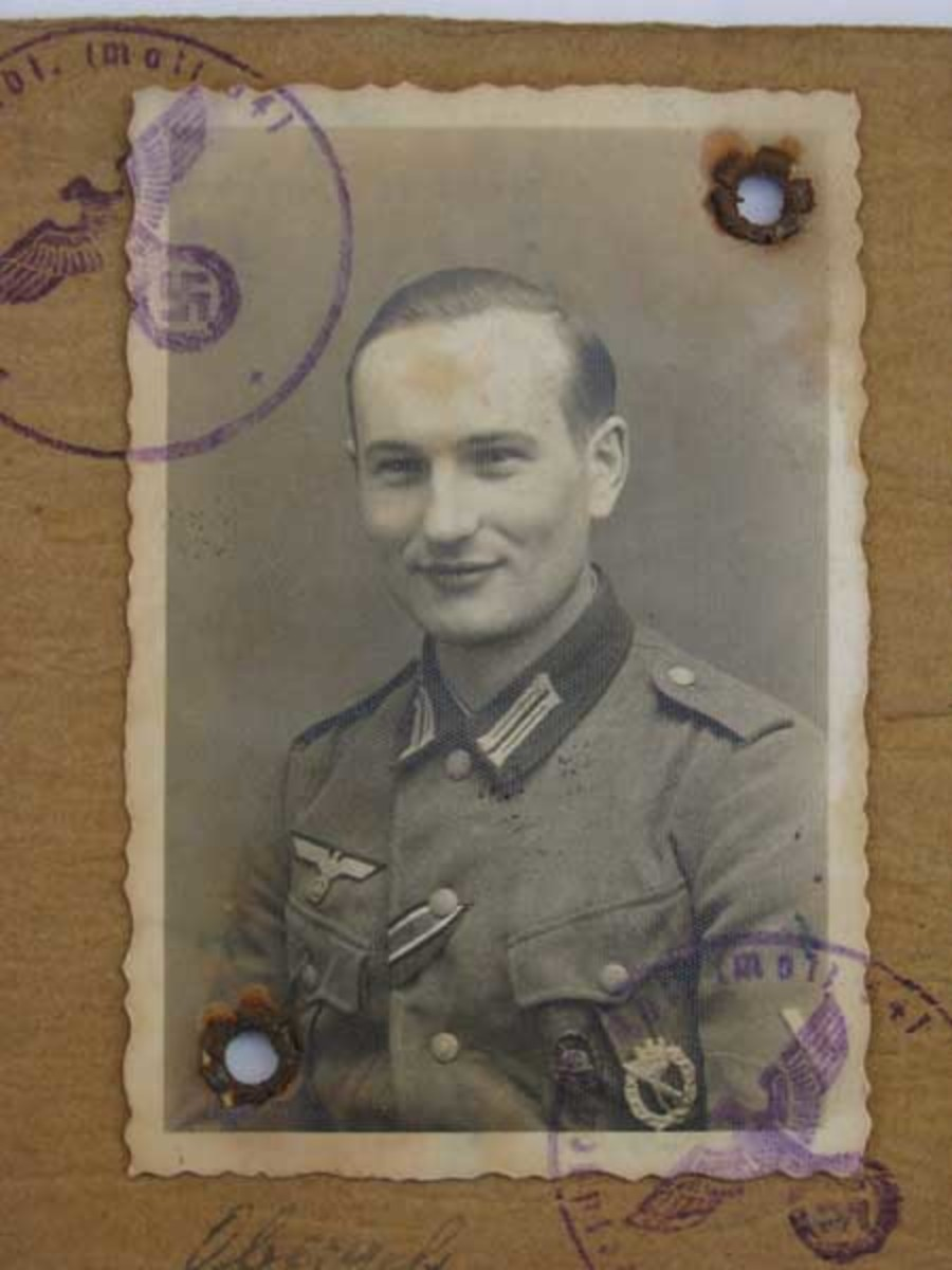 A well-decorated veteran of the Russian front sports a wound badge along with his other awards in this Soldbuch photo.