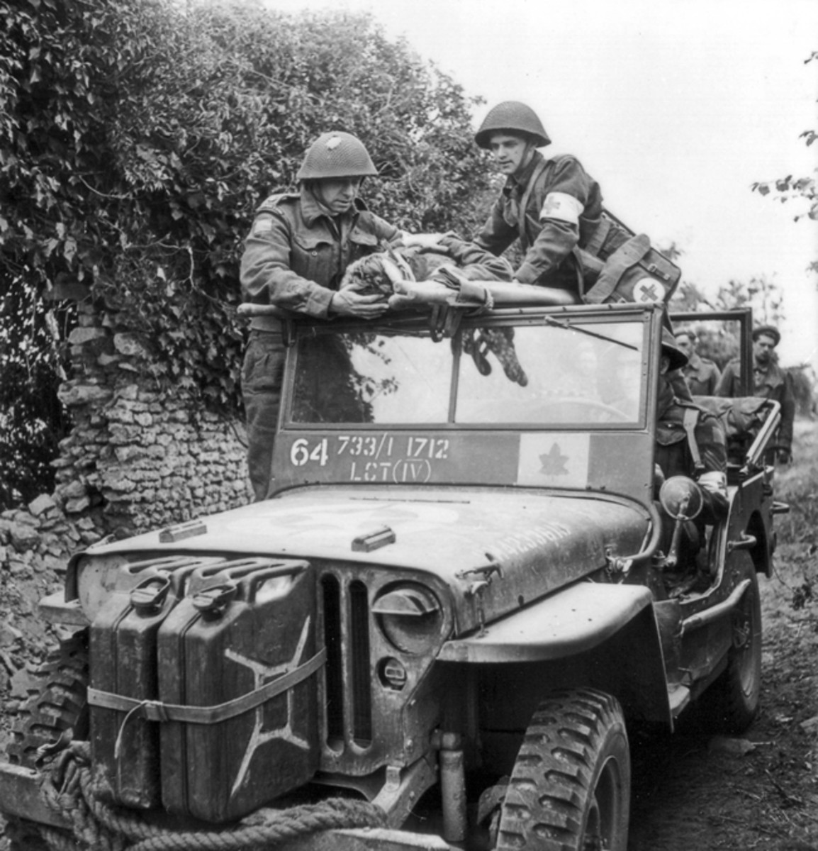 Canadian medical personnel and a chaplain from the Canadian 3rd Infantry Division use a Jeep to evacuate wounded soldiers during the fighting in the vicinity of Caen, France, July 15, 1944.