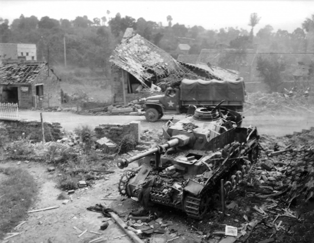 While the WC-54 was the standard frontline ambulance of US troops, extreme circumstances required extreme adaptations. Here, a CCKW bearing a Red Cross flag transports wounded soldiers past a German medium tank Panzer IV Ausf J from the 2nd German Panzer Division near Pont-Farcy, Normandy, France, in August 1944.