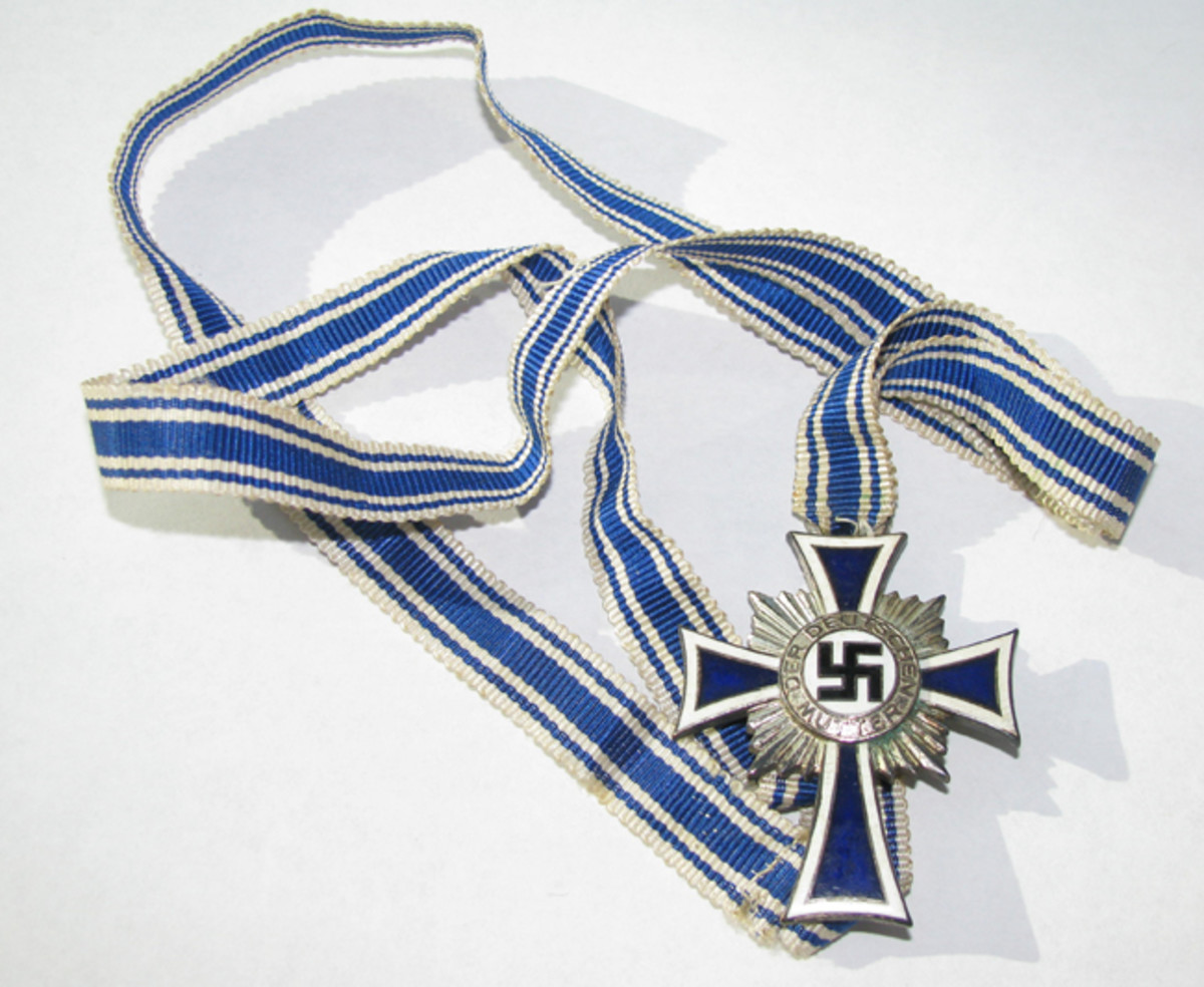 A silver Mother's Cross with long issue ribbon, the ends sewn together to enable the award to be worn around the recipients neck.