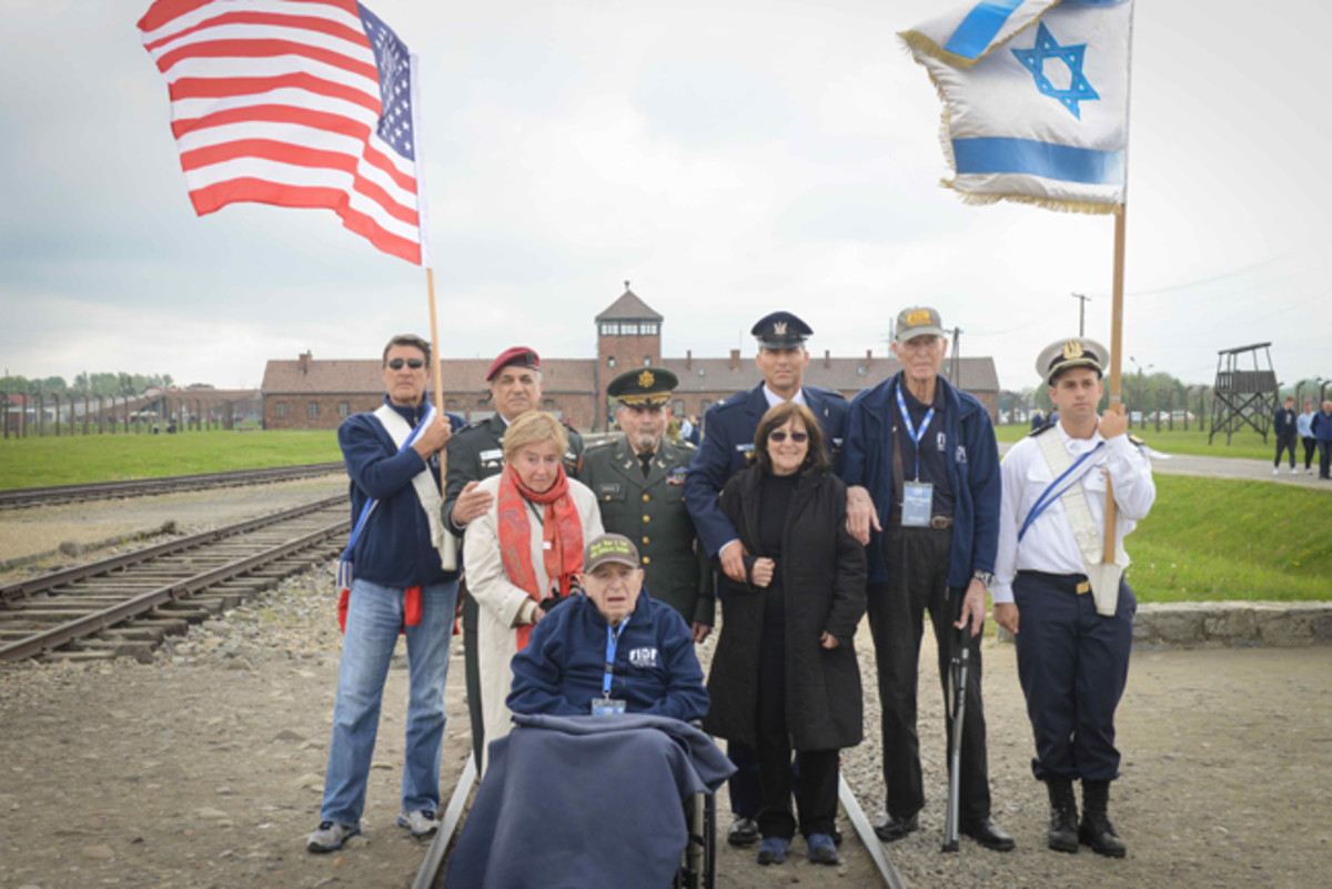 (From left, back row) An FIDF supporter bearing the American flag; FIDF National Director and CEO Maj. Gen. (Res.) Meir Klifi-Amir; American liberator Col. (ret.) Cranston Rogers, 90, of Medway, Mass.; Head of Israel's Helicopters Air Division Brig. Gen. Yaron Rozen; Lt. Col. (ret.) William Bryant Phelps, 90, of San Antonio, Texas, who liberated Mauthausen-Gusen with the 11th Armored Division; an IDF officer bearing the Israeli flag; (from left, middle row) Auschwitz survivors Giselle Cycowicz and Martha Weiss; and (front row) Sid Shafner, 94, of Denver, Colo., who was one of the first U.S. soldiers to enter Dachau with the 42nd Infantry Division and was awarded two bronze stars for heroism, on the tracks leading to the Birkenau camp (Auschwitz II) in Poland.