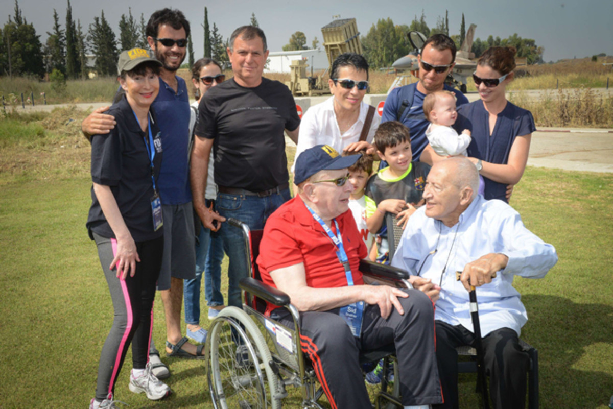 Sid Shafner and Holocaust survivor Marcel Levy, whom Shafner liberated from Dachau, reuniting for the first time in 21 years at an Israeli Air Force base. Behind them are Shafner's daughter, Elayne Feldman, and Levy's family.