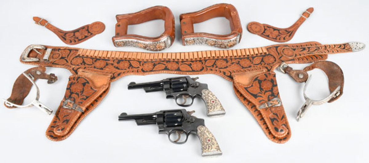 https://www.liveauctioneers.com/item/58862506_john-wayne-3844-hd-smith-wesson-custom-revolvers Two 1932 Smith & Wesson matching .38/.44 fixed-sight revolvers, personal property of movie icon John Wayne, JW initials on grips, hand-tooled leather double holster with gold-overlaid, ruby-adorned silver buckles; stirrups, spurs.