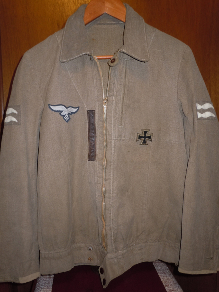 Not often encountered today, the tan cotton summer weight Luftwaffe Pilot jacket with EM breast eagle, zipper front, and waist band button snaps has two medal loops with an Iron Class first class medal (IC added on by the author) and Staff Sergeant rank insignia.
