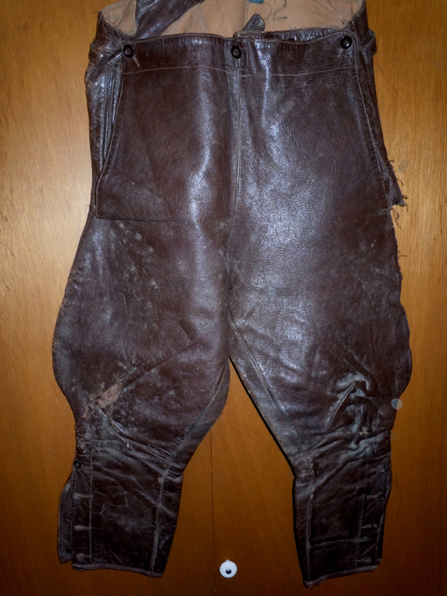 The leather flying breeches have a three button front and show wear on the knees and the leather is torn on lower seam of the left pocket.