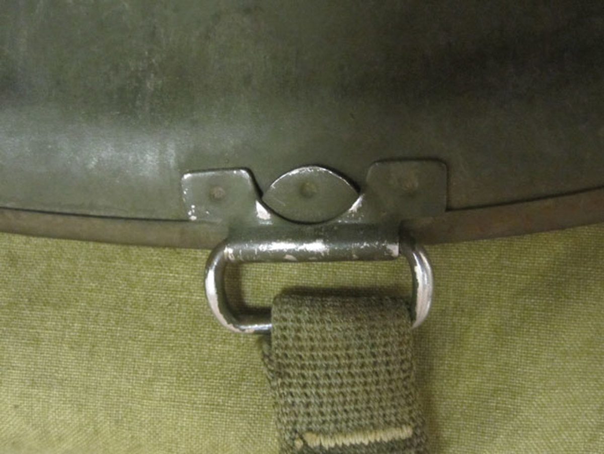 Originally, the chin straps were sewn onto fixed loops. This feature was installed on all front and early rear seamed helmets. The fixed loops were a weak point in the helmets design because the loops were in constant contact with the surface.
