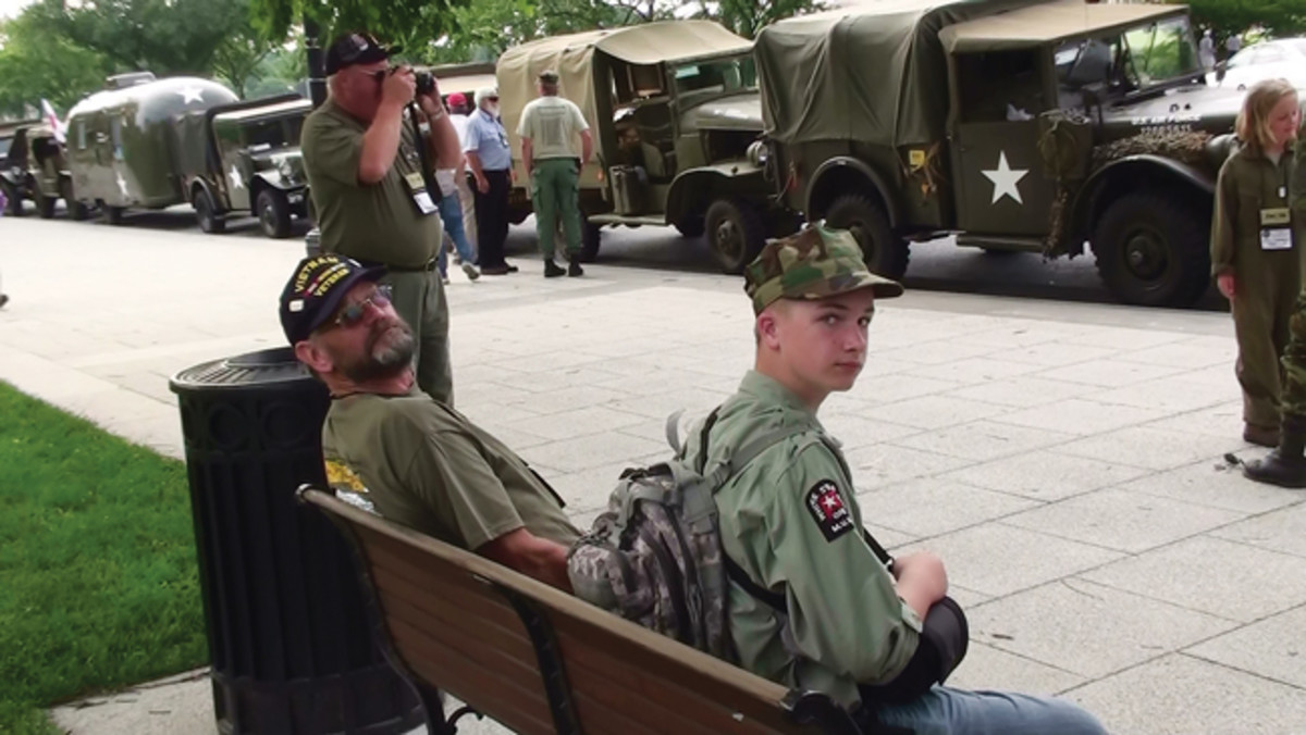 "Convoys are an ideal event to generate interest in HMVs. People and kids love a parade, veterans always show up, and the media is drawn to ""showy"" activities. Taken during the 2009 Lincoln Highway Convoy, pictured are (foreground): Unidentified; Don Tegtmeier; and young convoyers, Gunnar Sigrist and Julia Lawrence."