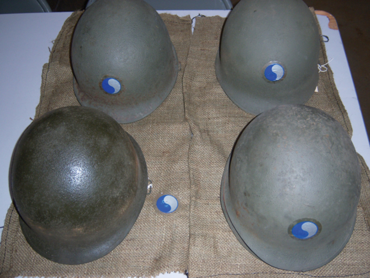 """A sample of the helmets showing the different paint shades and textures: first row Helmet #24 (left) and #1 (right); second row Helmet # 32 (Left) and #16 (right). Note that most helmets have still retained their 1994 """"50th Anniversary of D-Day"""" re-enactment 29th Infantry Division stickers. The large amphibious re-enactment took place at Fort Story, near Virginia Beach."""