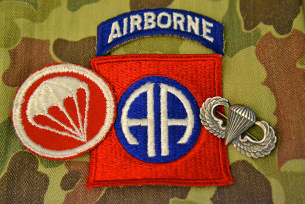 A good example of the World War II era cut edged 82nd Airborne Division patch, the airborne tab was authorized on 31 August 1942. This patch is flanked on the left with the field artillery parachute overseas cap insignia and on the right with the Parachute Badge designed by Captain (later Lieutenant General) William P. Yarborough who commanded the Division's 2nd Battalion, 504th Parachute Infantry Regiment during the war.