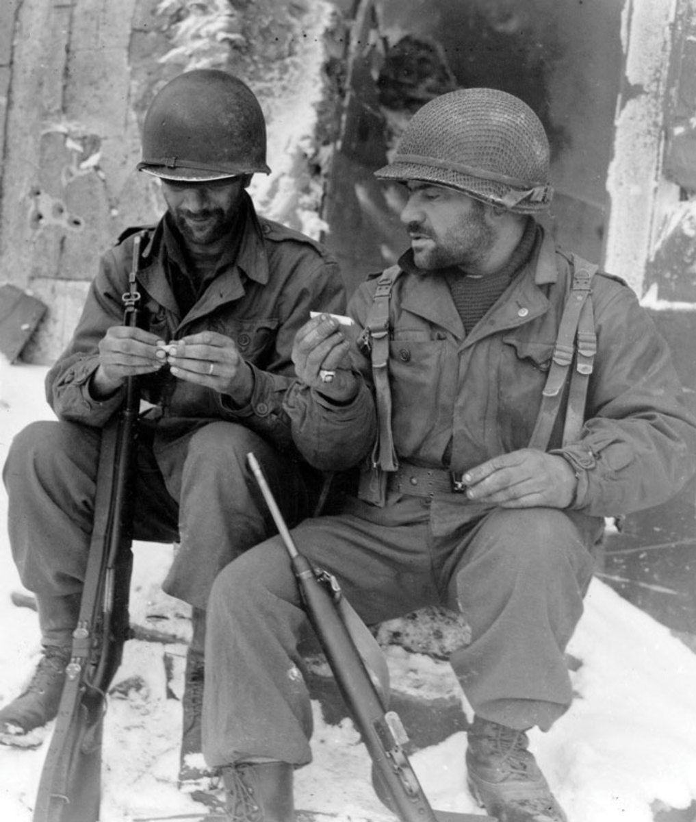 WWII Signal Corps photo showing two GIs wearing the M1 helmets on a smoke break during WWII . The soldier on the right wears a helmet with a late model helmet net and elastic foliage band while the helmet on the soldier on the left exhibits common paint loss to the helmet rim.
