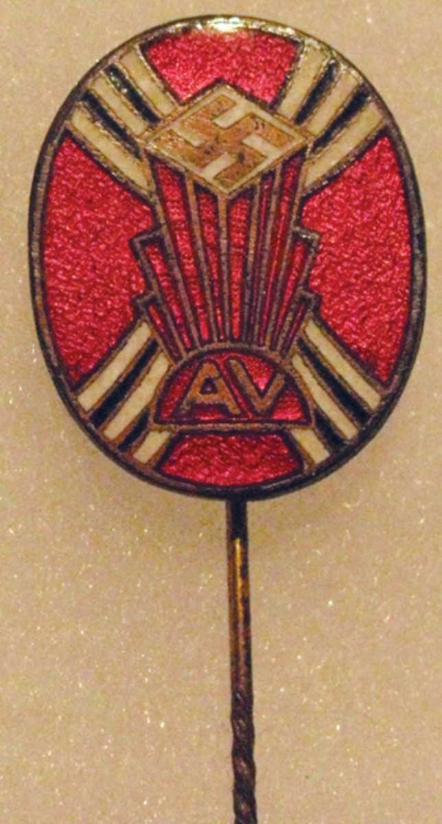 An enameled AV membership pin on a stickpin base.