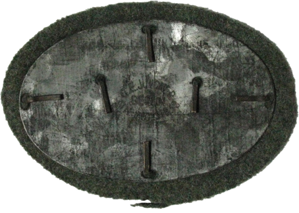 This metal Maschinengewehr Abzeichen made by Junckers is mounted on a gray-green wool backing that would blend well with a soldier's army uniform.