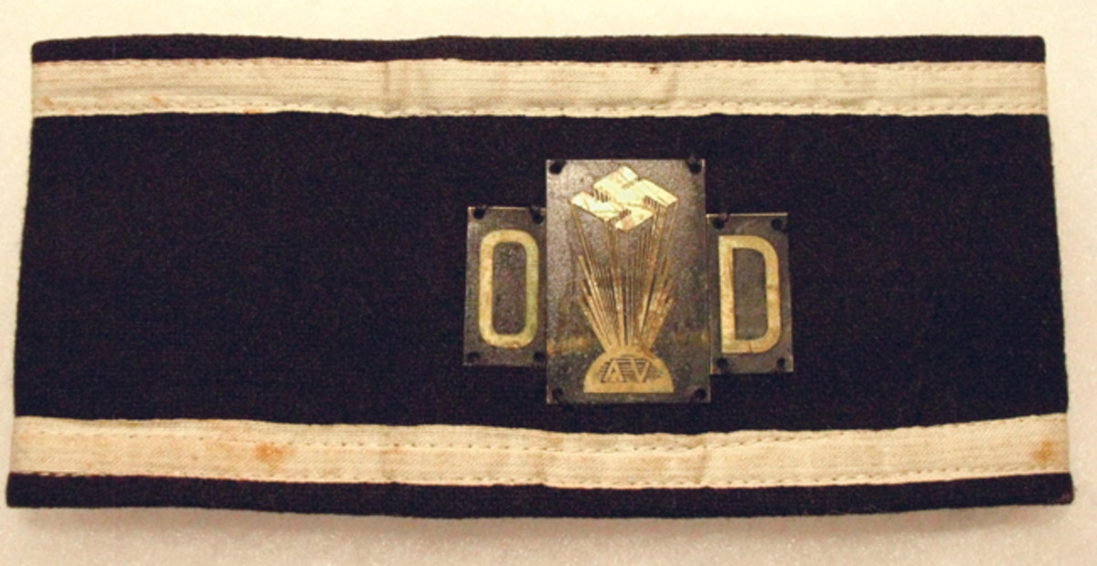 The Ordnungsdienst (OD — Order Service) was the American equivalent of the German Schutzstaffel (SS).This OD armband is made up of three tin plates sewn to a blue-black backing with white striped borders.