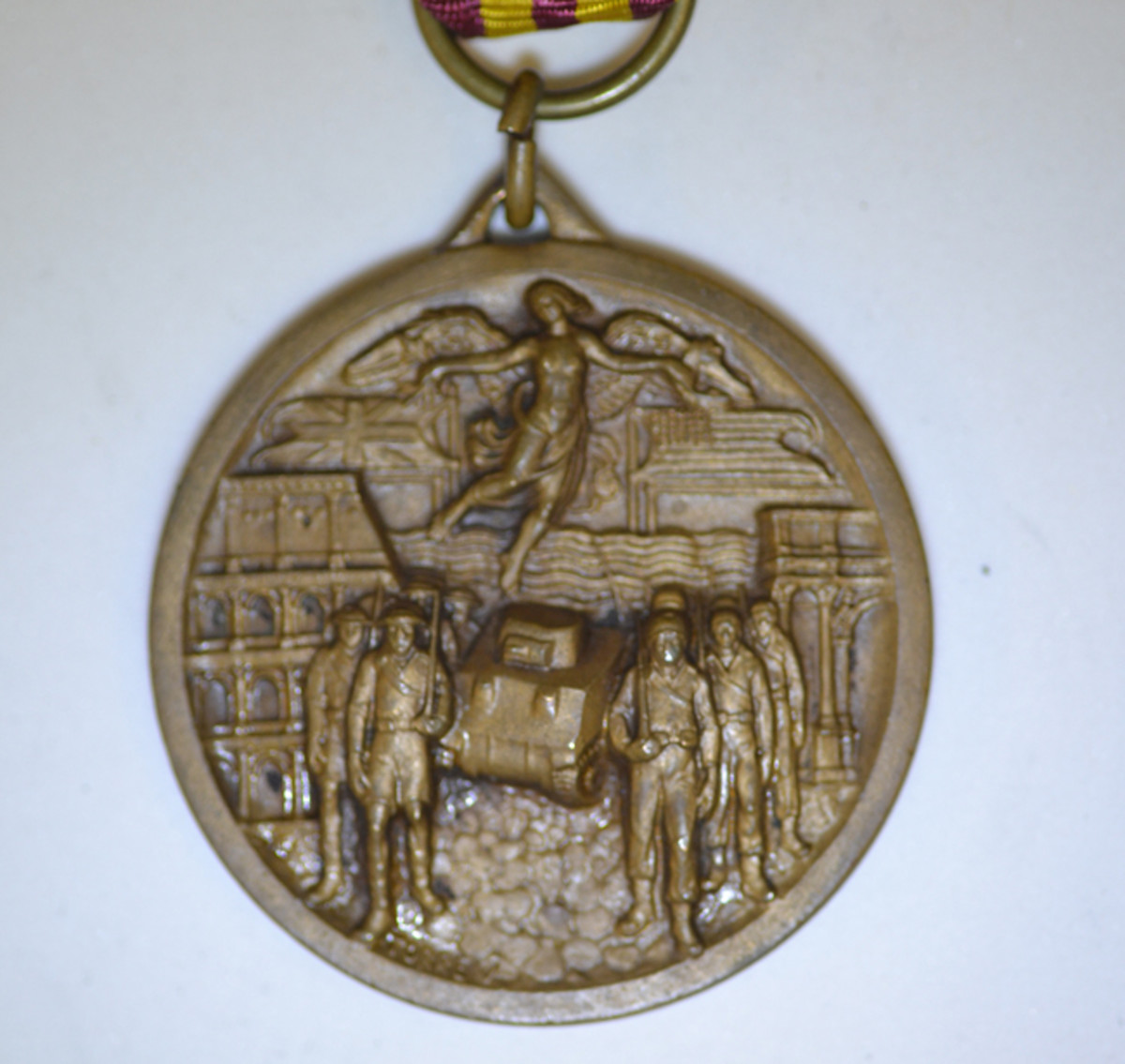 The Type 4 Liberation of Rome Medal show a high relief design of Allies and Tanks entering Rome under U.S. and British Flags with Lady of Victory. It also displays a maker's mark.