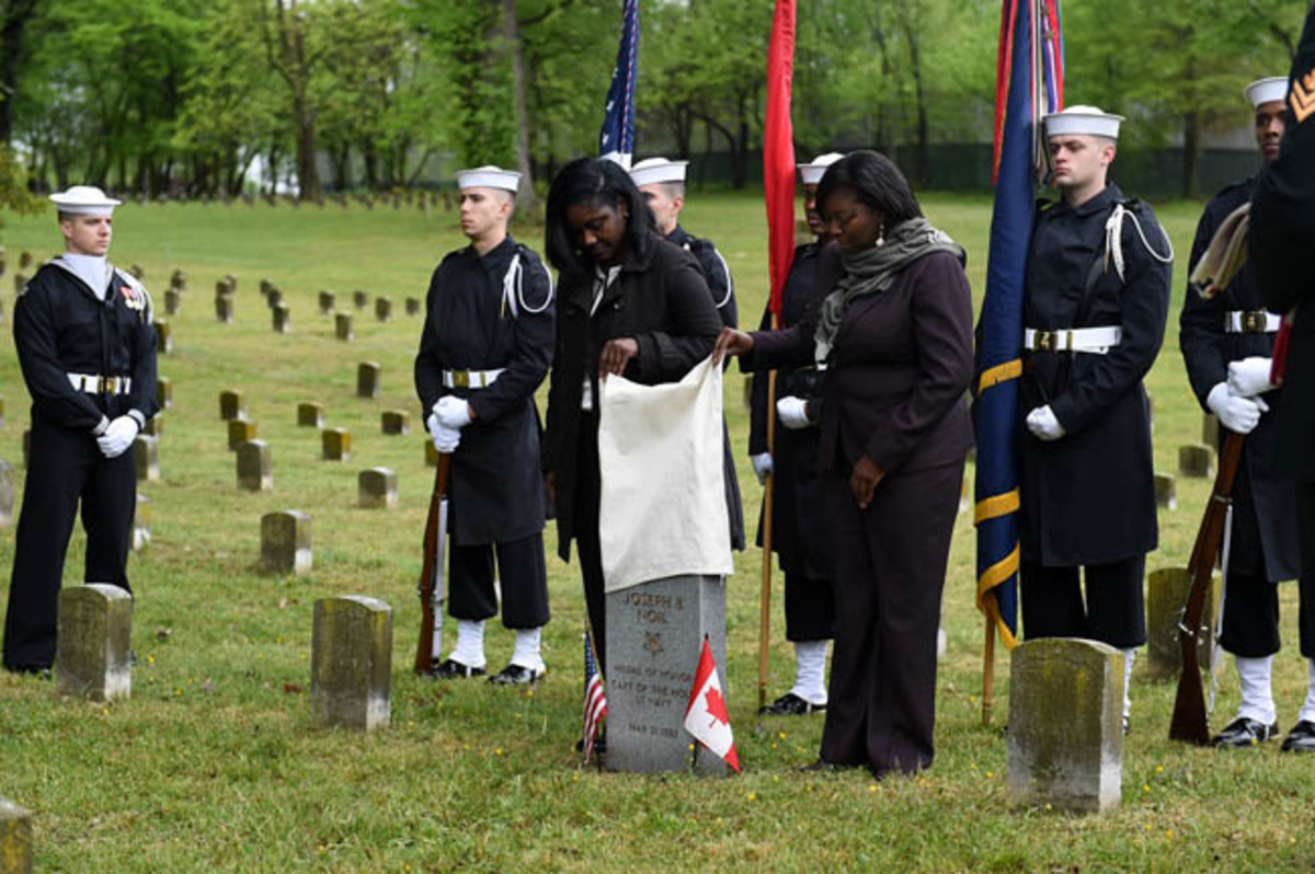 District of Columbia Executive Director of the Mayor's Office of Veterans Affairs Tammi Lambert, left, and Director of the Department of Behavioral Health Tanya A. Royster, M.D., right, unveil the headstone of Medal of Honor recipient Joseph B. Noil during a ceremony April 29, 2016 at St. Elizabeths Hospital Cemetery. Noil received the Medal of Honor while serving on USS Powhatan, but his headstone did not recognize his award due to a misprint on his death certificate. (U.S. Navy photo by Mass Communication Specialist 2nd Class Eric Lockwood/Released)