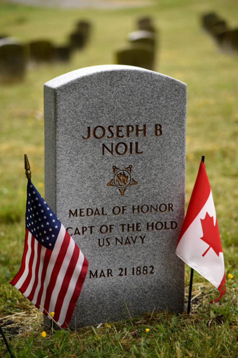 160429-N-TH437-182 WASHINGTON (April 29, 2016) American and Canadian flags are placed at the newly erected headstone of Medal of Honor recipient Joseph B. Noil during a ceremony April 29, 2016 at St. Elizabeths Hospital Cemetery. Noil received the Medal of Honor while serving on USS Powhatan, but his headstone did not recognize his award due to a misprint on his death certificate. (U.S. Navy photo by Mass Communication Specialist 2nd Class Eric Lockwood/Released)