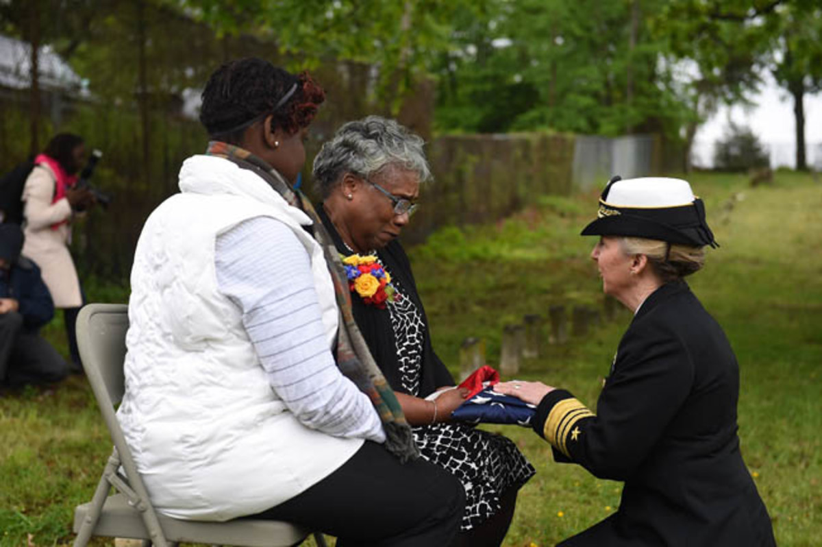 Chief of Navy Reserve Vice Adm. Robin Braun presents the American flag to Bernadette Maybelle Parks Ricks, great granddaughter of Medal of Honor recipient Joseph B. Noil during a ceremony April 29, 2016 at St. Elizabeths Hospital Cemetery. Noil received the Medal of Honor while serving on USS Powhatan, but his headstone did not recognize his award due to a misprint on his death certificate. (U.S. Navy photo by Mass Communication Specialist 2nd Class Eric Lockwood/Released)