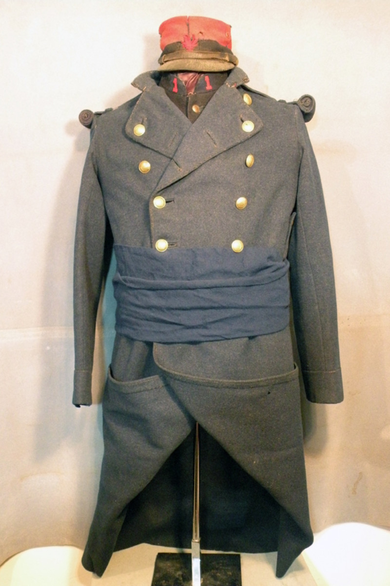 Uniform of a member of the 1st Marching Regiment, 1st Foreign Legion consisting of the Model 1877 dark blue overcoat, Model 1870 dark blue tunic with collar numerals in red and the Model 1884 kepi.