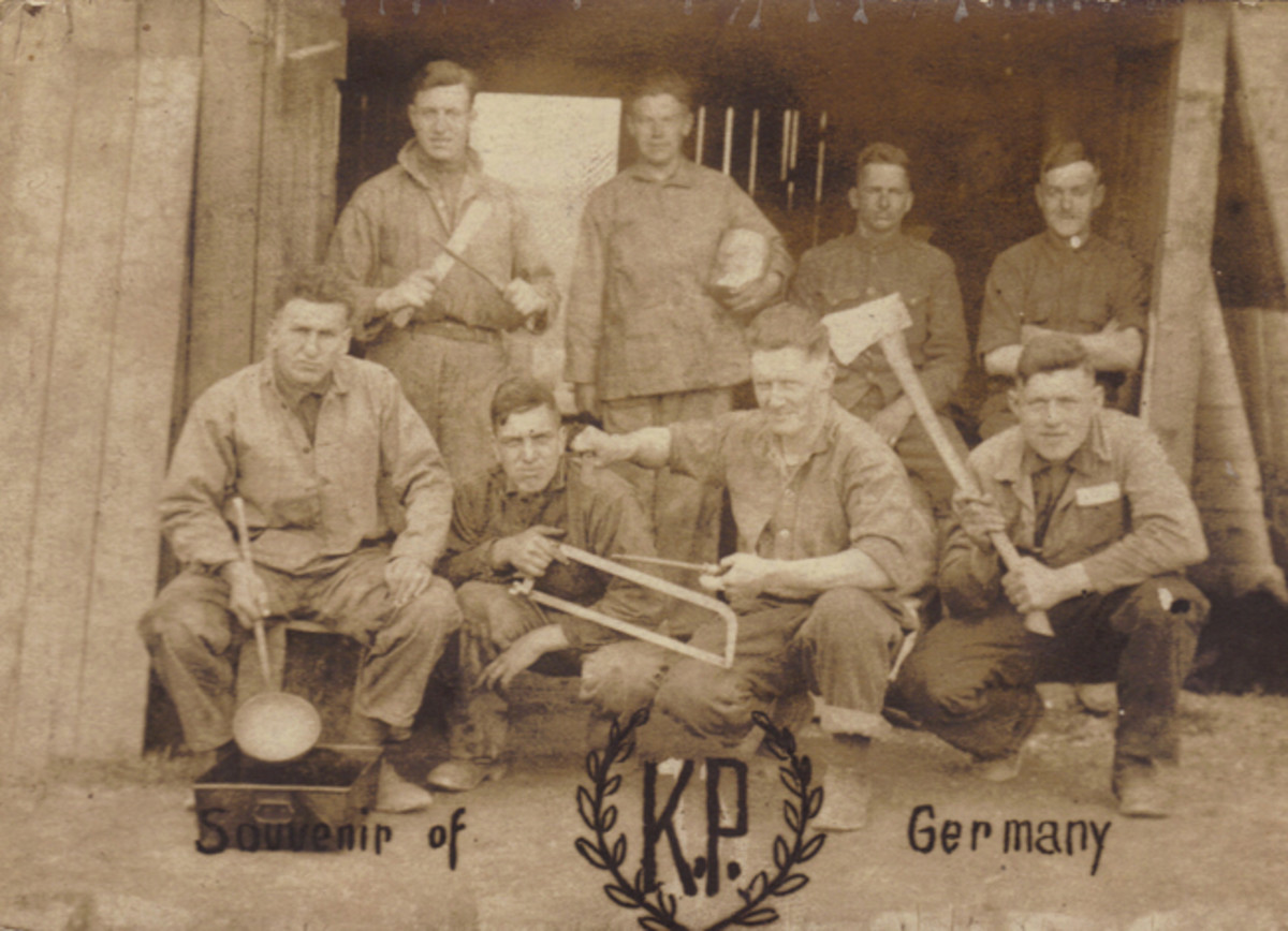 """This image gives us an idea of what passed for humor in the mess sections of the Big Red One. Brandishing all of the sharp tools of their trade, these Doughboys of the 1st Division threaten each other playfully. During the occupation of Germany, many 1st Division photos portrayed the Division's symbolic number """"1"""" inside a wreath and these soldiers have replaced it with their current assignment: Kitchen Police."""
