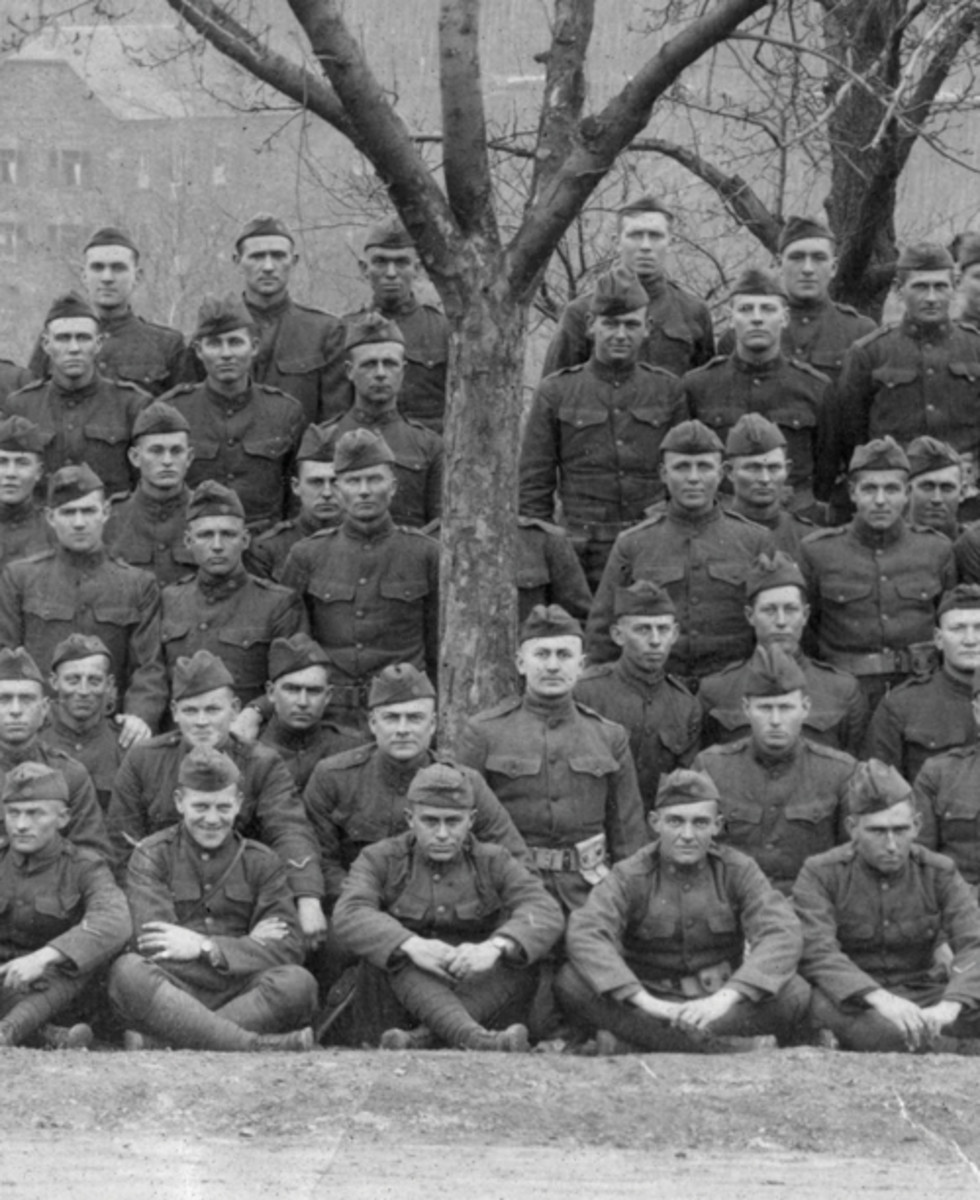 """More 90th Division humor or accidental placement? The artillerymen from Battery """"F"""", 345th Field Artillery Regiment, pose for a """"yard-long"""" photo. The soldier in the center behind the tree was either the unit comedian or just unlucky; either way, he had to know he was not going to be in the photograph. What was he thinking? (Photo courtesy USAMHI)"""