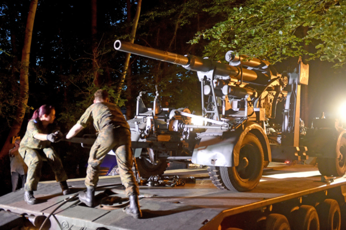 A WWII-era flak canon is prepared to be transported from the residential site.