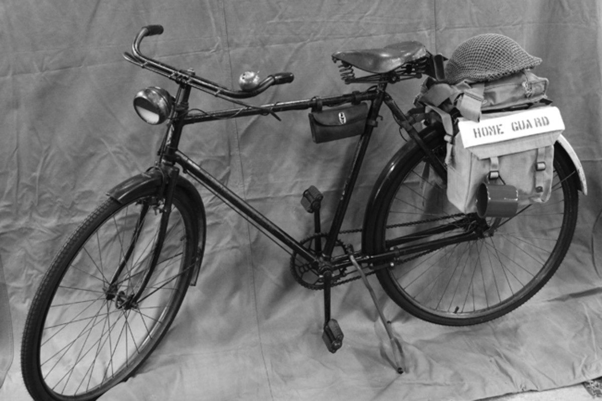 """A true """"survivor,"""" this original-condition British BSA Mark V* WWII bicycle is displayed with a Home Guard helmet and gas mask respirator."""