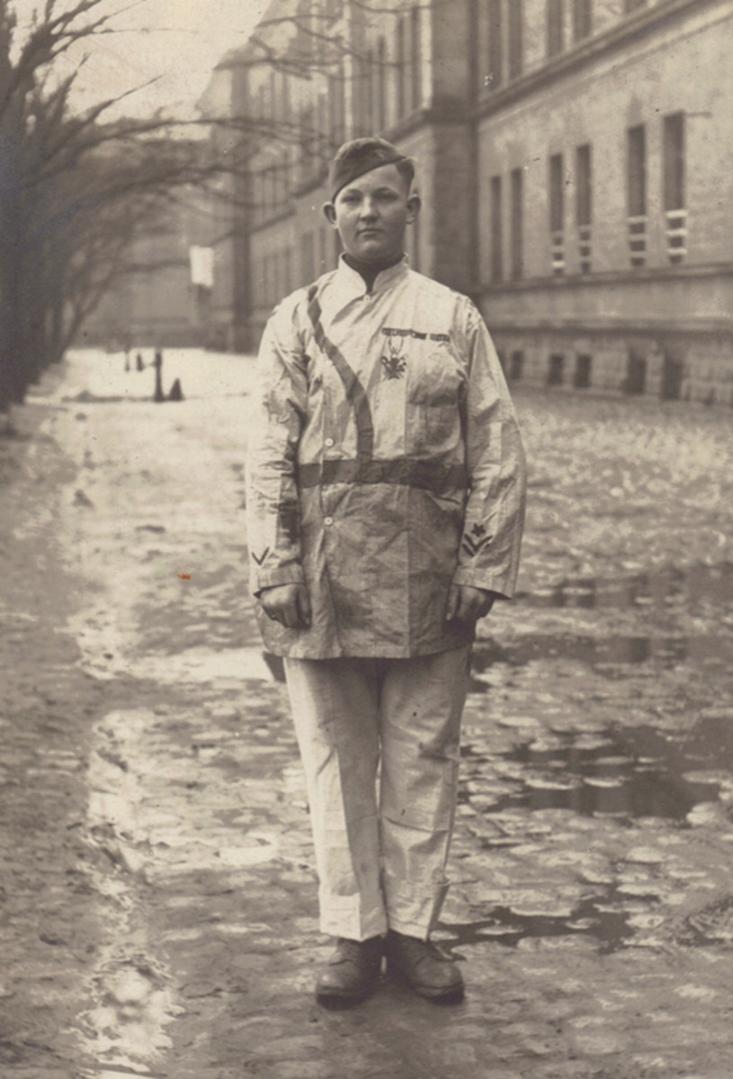 """A real head-scratcher; this orderly from the 19th Evacuation Hospital, located near Trier, Germany, has decorated his white over-garments with a Sam Browne belt, Croix de Guerre, a row of ribbons, two overseas stripes and an """"early arrival in France"""" star."""