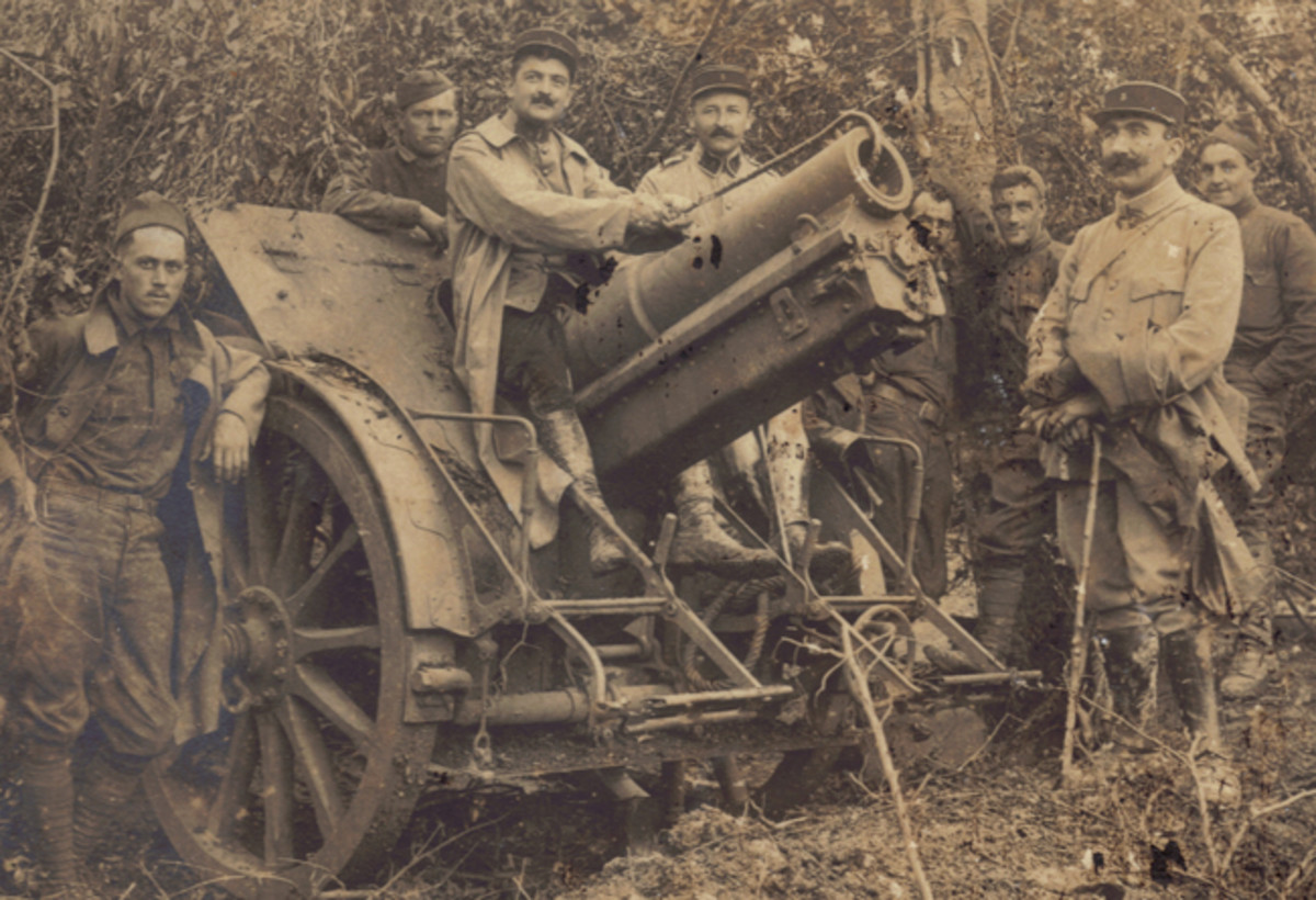 A solemn group of 37th Division artillerymen and their French 5th Regiment comrades pose with a captured German field piece. Only the Doughboy on the far right seems to see the humor in the pose of the Frenchman seated on the cannon barrel.