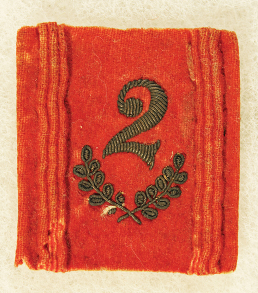 An example of the pre-1871 red square wool cockade with gold bullion embroidered battalion number.