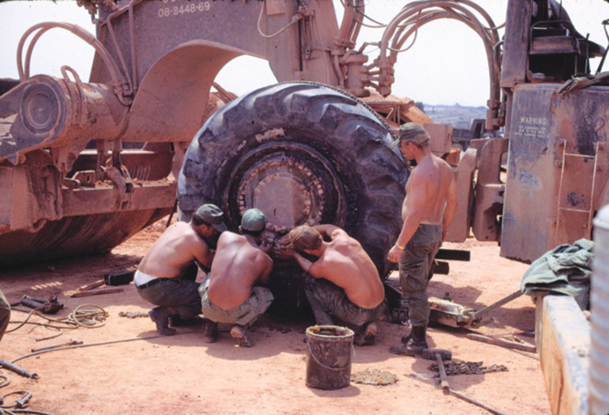 "Changing one of the biggest ""flat tires"" on a Clark Pan Scraper in Bien Hoa, 1972. The Engineers were trying to inflate it with an M52A2, but it wasn't going well for them"