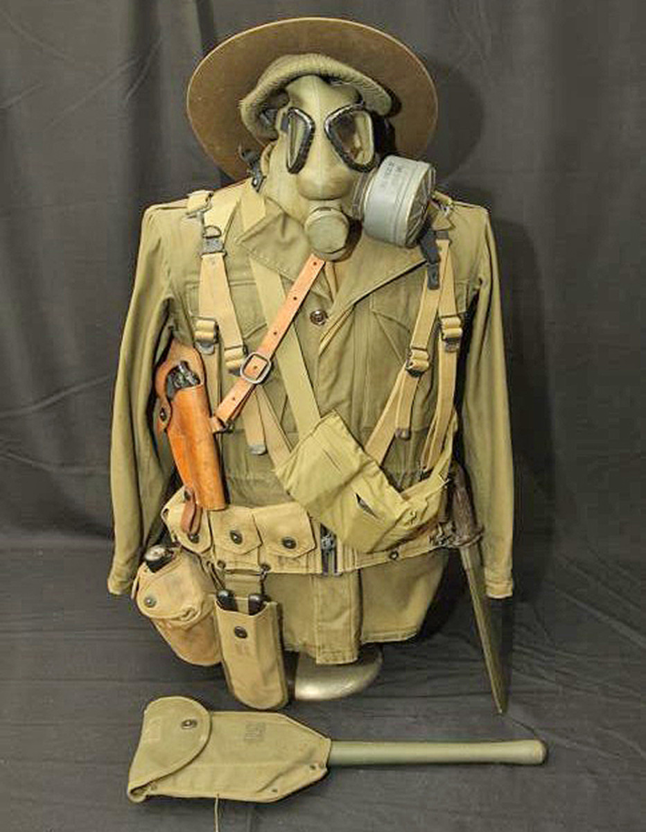 Military uniform top with accessories including gloves, gas mask, bayonet, wire cutters, hat, gun holster, canteen, ammunition holder sold for $346.