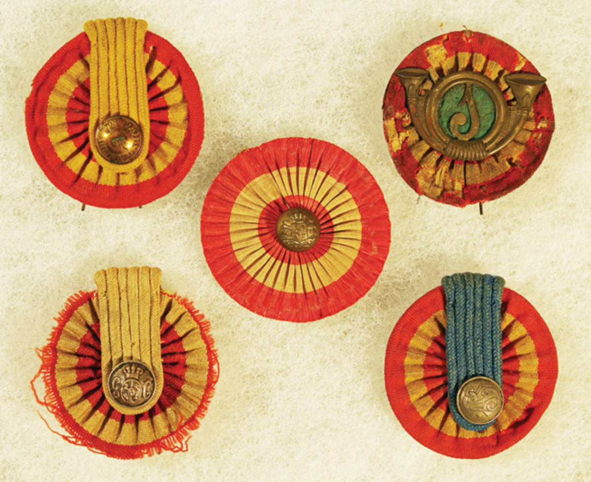 "Cockades Issued in Puerto Rico: Top row: Volunteers of Puerto Rico, Non-regulation volunteer cockade with Light Infantry insignia. Bottom row: Civil Guard, Municipal Police of San Juan, ""Universal"" cockade made of silk. This is one of the cockades issued as a souvenir to a soldier in the 6th Mass. Volunteers."
