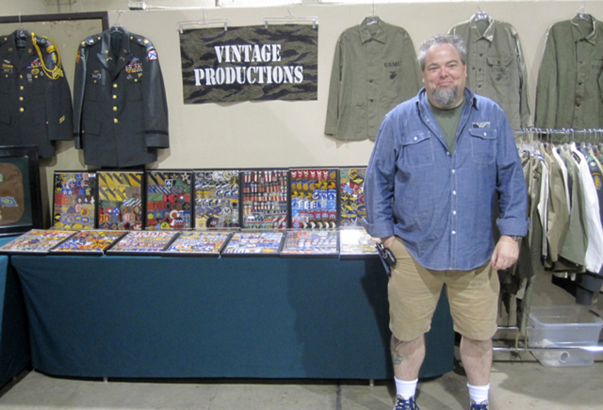 "Bob Chatt in front of his ""Vintage Productions "" booth that provided collectors with a good selection of quality WWII through Vietnam War era clothing and field gear and a dizzying array of original SSI and other insignia. Bob was pleased with acquiring the largest hall in the fair grounds and the overall attendance for the show."