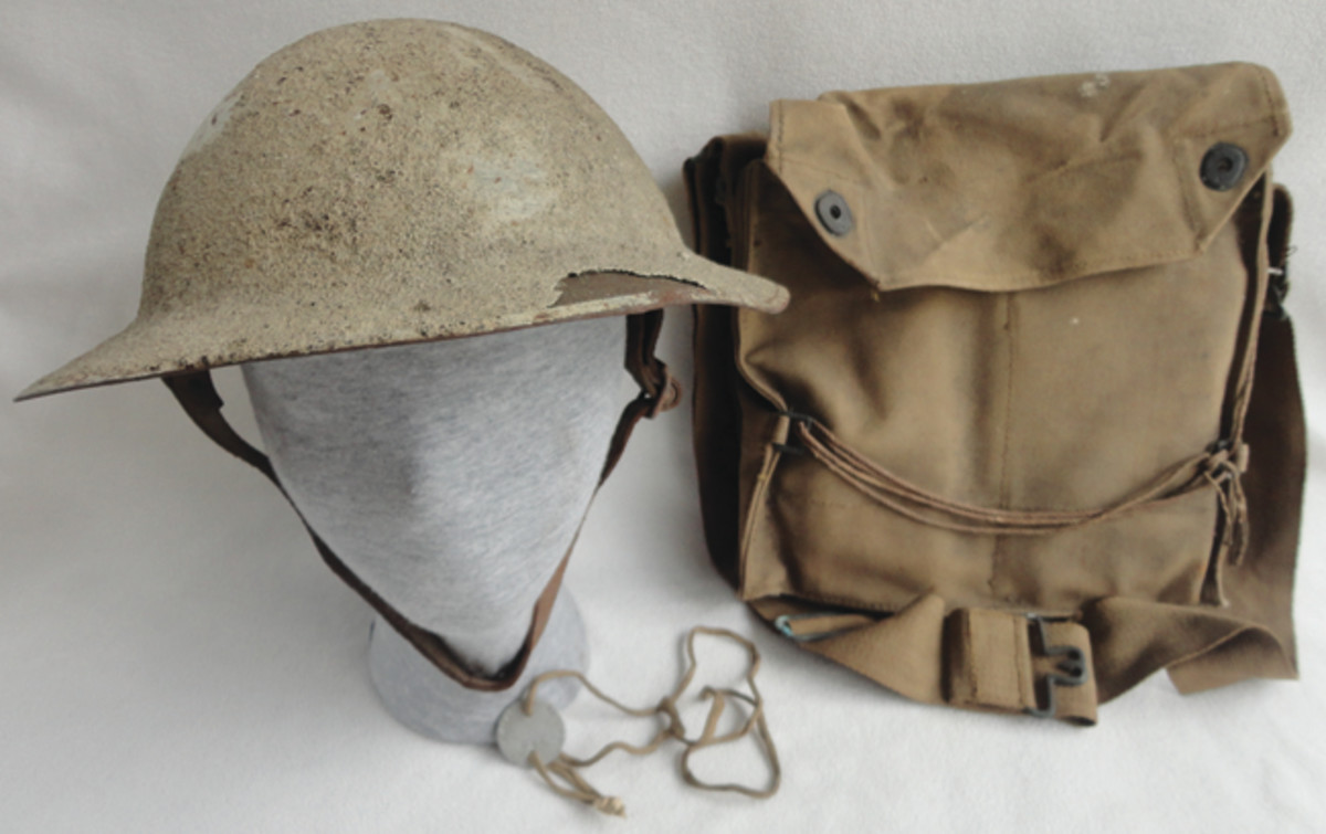 """iccum's white-painted helmet and gas mask bag. The bag has Niccum's name and """"MG Co."""" written on it."""