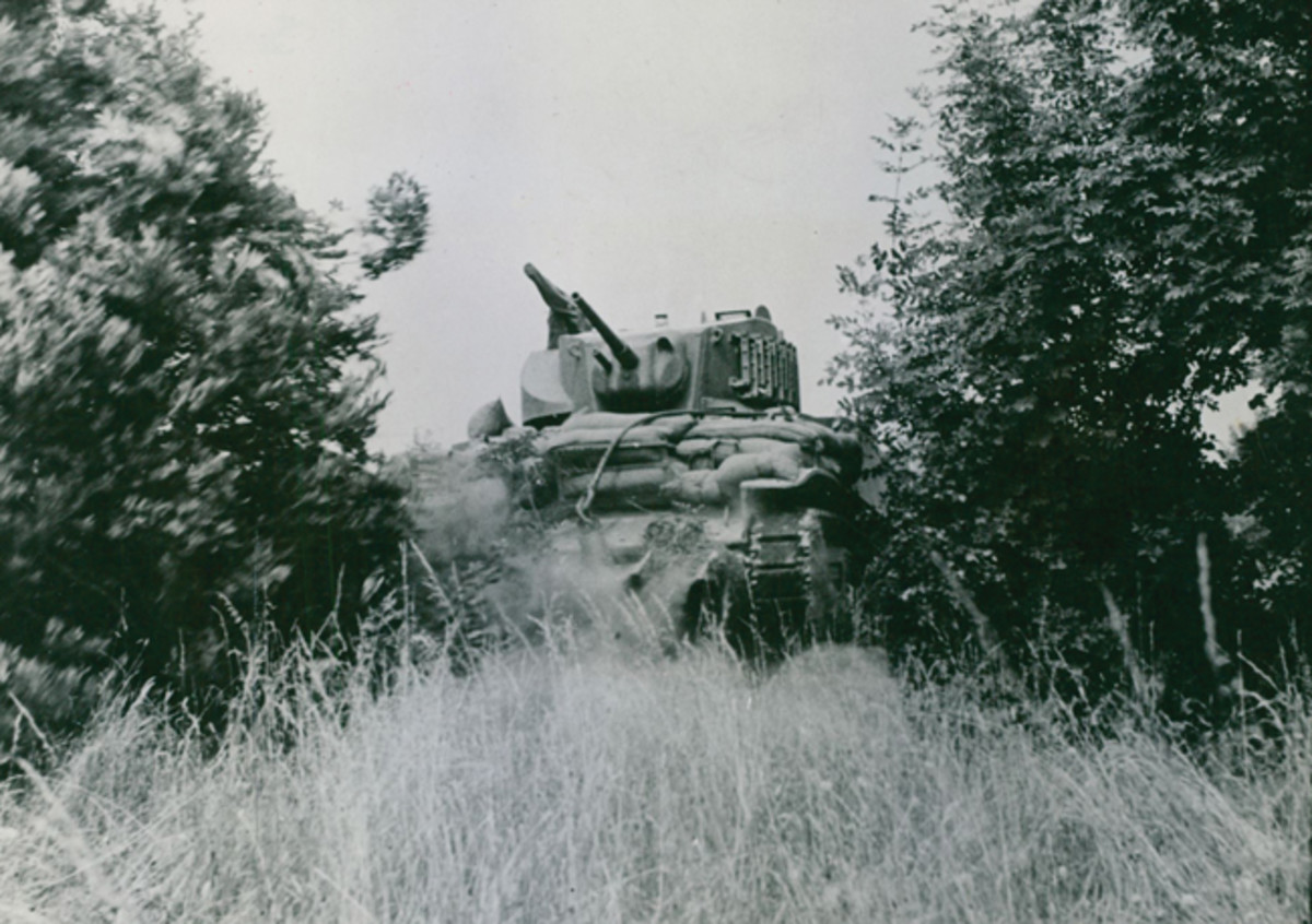 Historic photo of a Stuart tank pushing over a hedgerow.