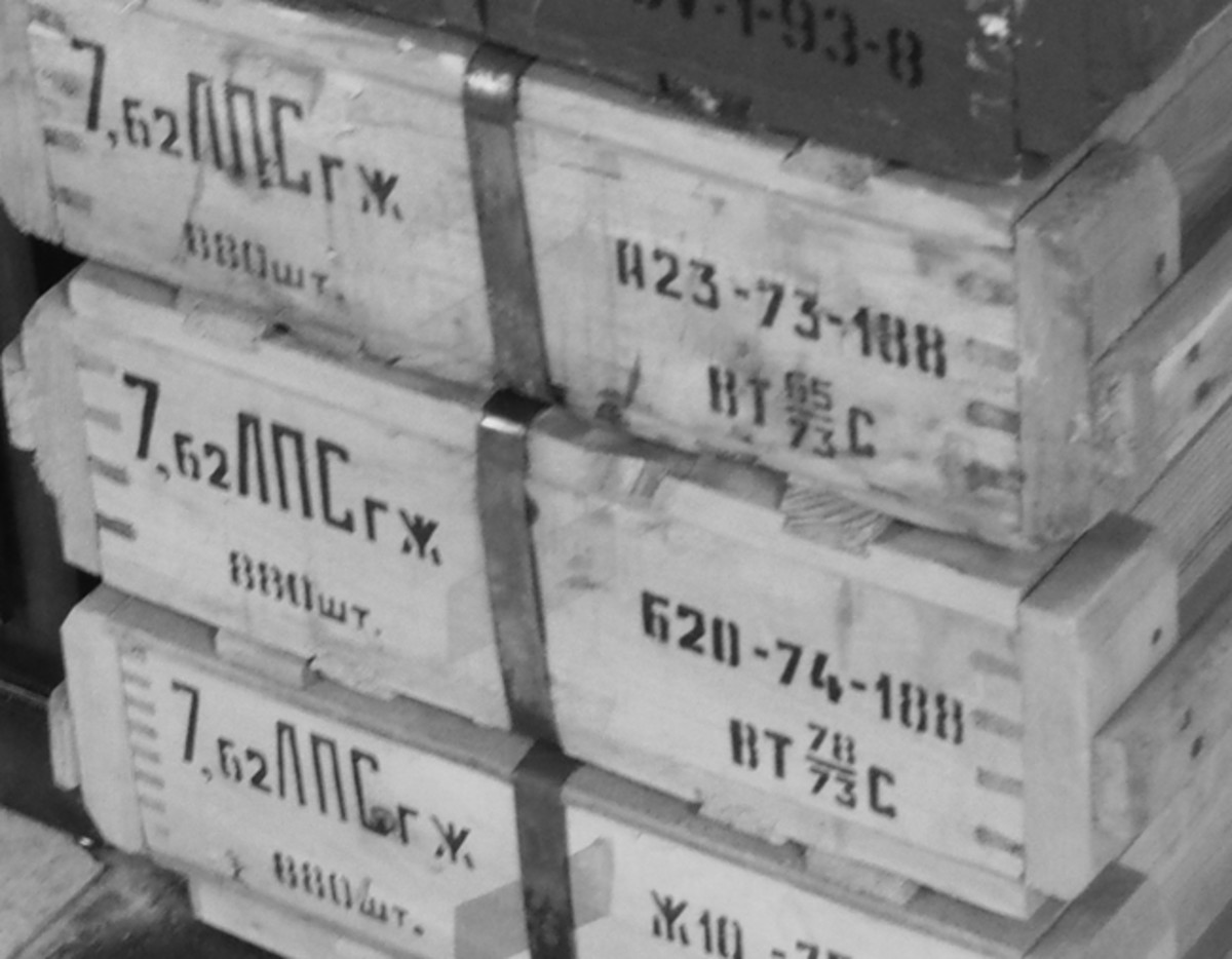 "With some understanding of the codes it isn't too hard to know what is in each of these wooden crates, which are nailed shut along with a metal strap. In each crate are two metal ""spam"" tins of ammunition."