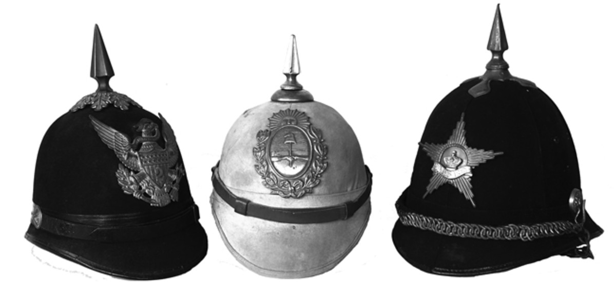 "Three very different ""spiked helmets"" – An American Model 1902 artillery spiked helmet (left), made of felt it was the final pattern of dressed helmets that had been in use since the 1870s; Argentine Model 1908 sun helmet, made of cork and covered in a canvas twill, it features a spike closer to the British pattern; and a post-World War II Dutch spiked helmet of Garderegiment Fuseliers Prinses Irene (right),which was introduced in 1966 and is still used as the unit's formal headdress. (Collection of the Author)"