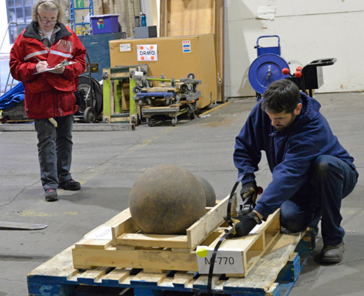 Lea Davis, Naval History and Heritage Command curator, keeps track of the information on a pallet of cannon balls for the bill of lading, as a contractor from McCollister's Transportation Group secures them for transport. The company is moving artifacts from the command's warehouse and Cold War Gallery to a new facility in Richmond. (U.S. Navy photo by Mass Communication Specialist First Class Tim Comerford/RELEASED)