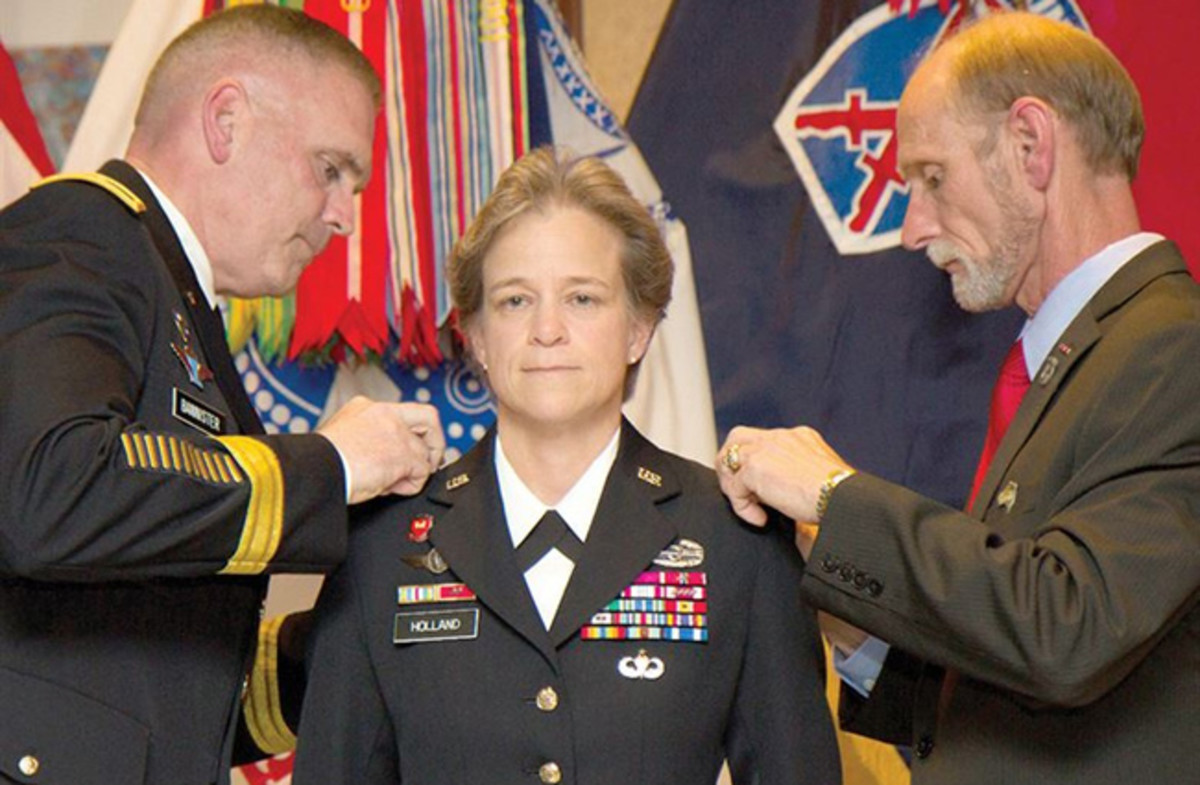 Brig. Gen. Diana Holland becomes the first woman to hold the title of deputy commanding general for support in a light infantry division during her promotion ceremony to brigadier general on Fort Drum, N.Y., July 29, 2015. Her husband, James Holland Jr., right, and Army Maj. Gen. Jeffrey L. Bannister, 10th Mountain Division and Fort Drum commander, pin on her stars.