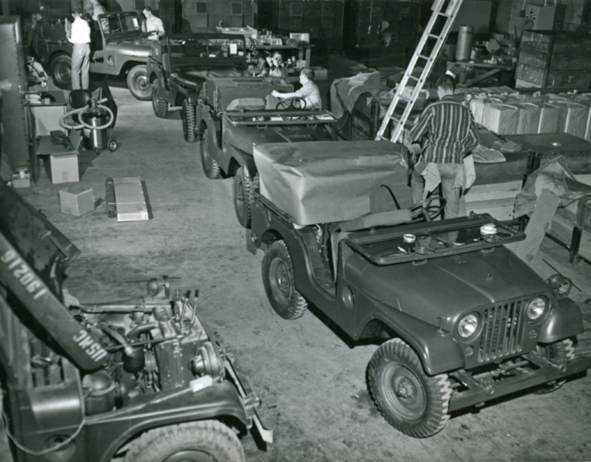 "Here's a photo of the MRC-83 production floor at Alpha near Dallas, Texas. In the foreground is an M38A1 with a TRC-75 1kW HF radio installed, the radio is under a protective wrap. Behind the first jeep is another, the radio is visible but has it's front watertight cover installed. Third jeep ditto, fourth jeep ditto. Lower left is a jeep that looks to be in the middle of an alternator install. Middle left on the floor appears to be accessories for the MRC-83 in a cardboard box banded together with an AT-1011/U in it's canvas case. visible at the top of the photo are four TSC-15 ""Communications Central"" radio shelters, shown with their vent covers open."