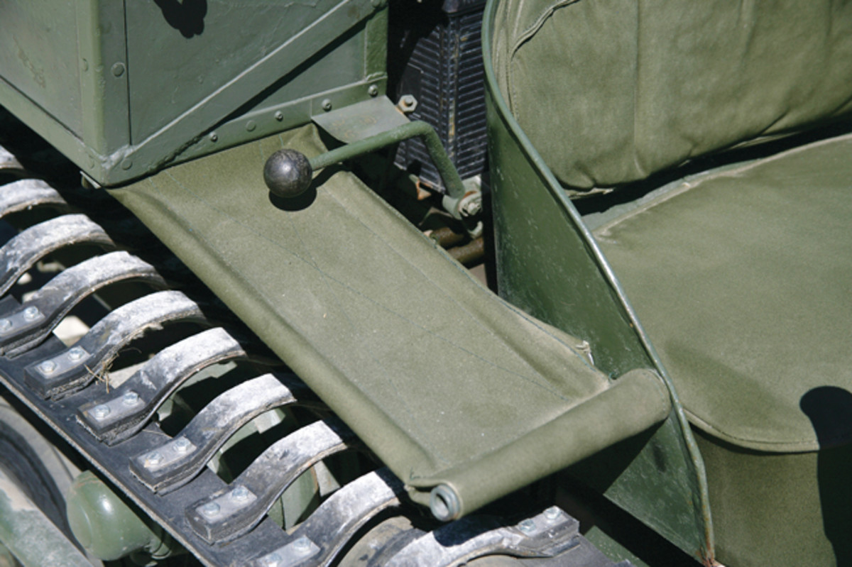 Front fenders made using a steel frame covered with stretched canvas provided some protection from flying debris and would retract when contacting any type of solid resistance. The short lever is for selecting from three forward and one reverse gear.