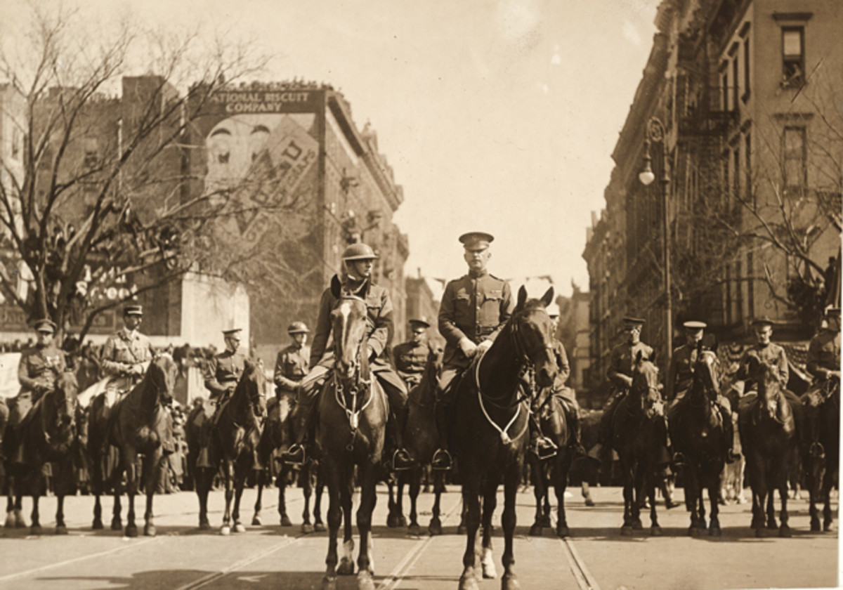 """The famous fighters who broke the """"Hindenburg Line"""" march down 5th Avenue, New York, between throngs of people from all parts of the country. General O'Ryan reviewed men as they marched by on parade to the warm welcome."""