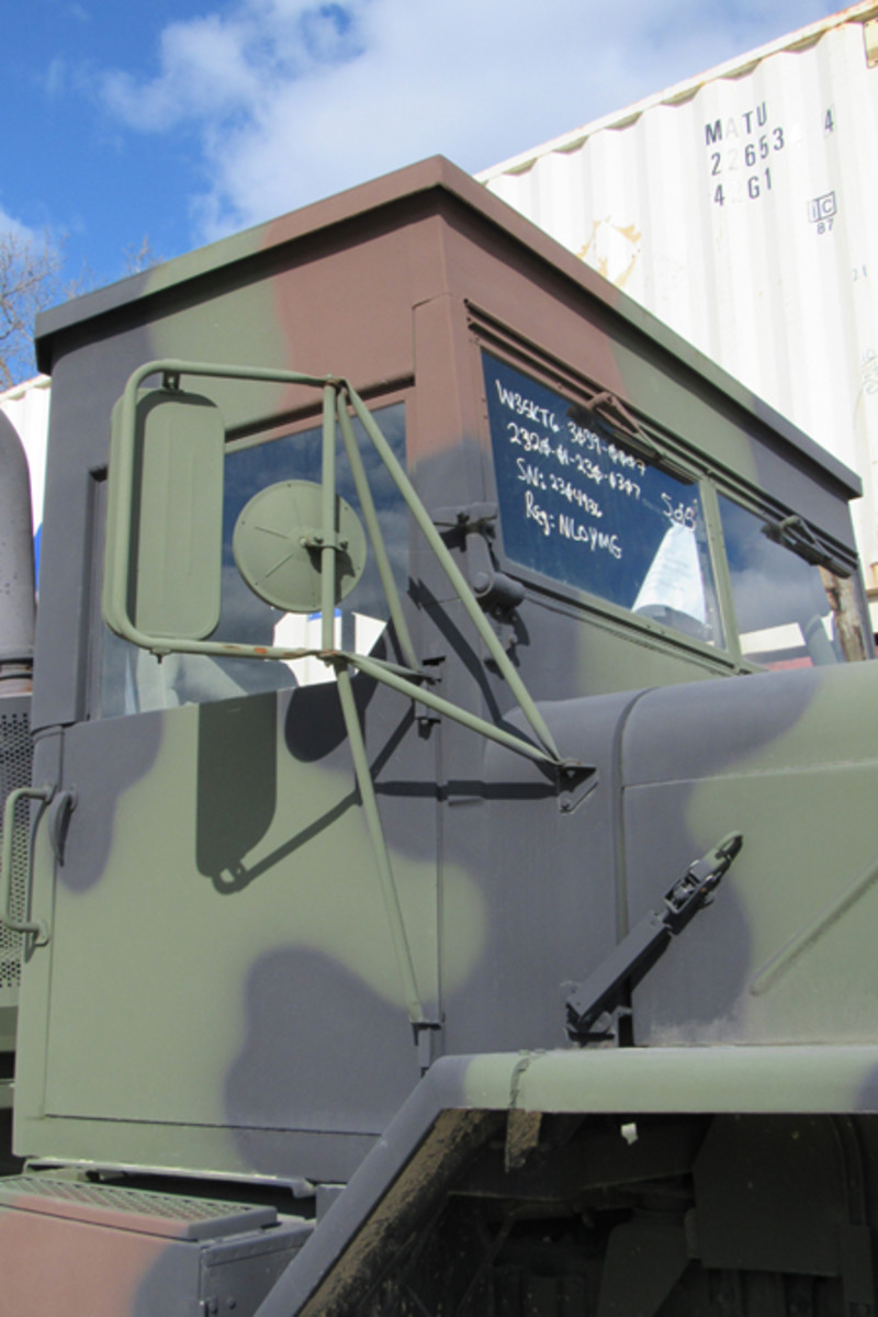 This side view shows the lack of air vents at the bottom of the cab. Behind the mirror bracket, the handle to fold the windshield down is visible. While the windshield fold panels fold out like any other M939 truck, the top has to be removed, before you can fold down the windshield.