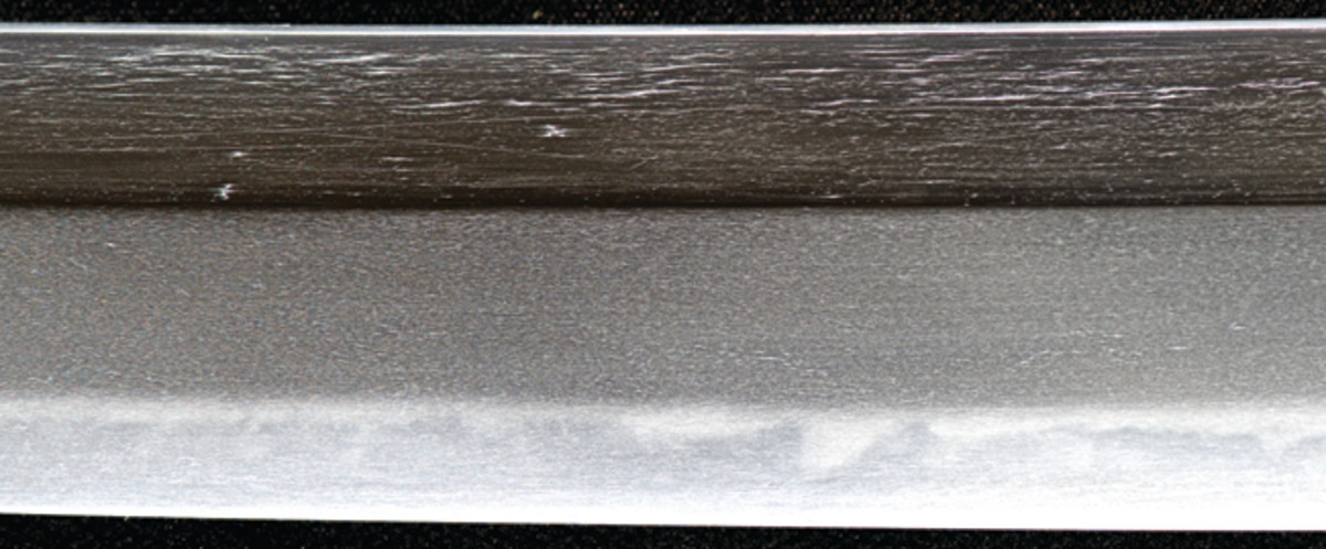 A sword by Masatsugu features a visible surface pattern or jihada on the blade. The thin white lines form the jihada, and the lines form short and somewhat discontinuous tracks on the surface. The blade probably is made from 19th-century puddled steel.