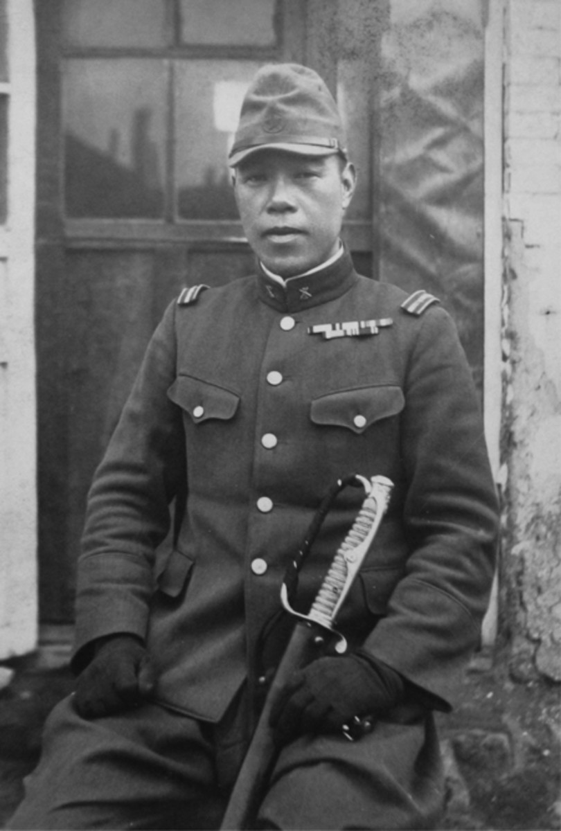 "A Japanese first lieutenant in a 1930-31 uniform holds an 1886-style kyu-gunto sword mounting. Note the large ""D"" ring over the hilt."