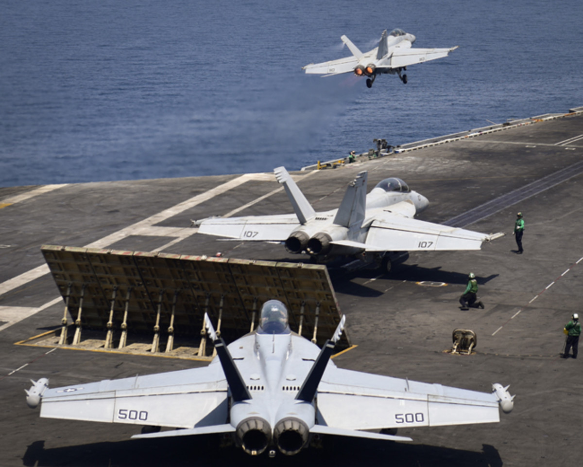 "ARABIAN GULF (July 29, 2017) An F/A-18F Super Hornet from, the ""Black Knights"" of Strike Fighter Squadron (VFA) 154, launches from the flight deck of the aircraft carrier USS Nimitz (CVN 68) while another Super Hornet from the ""Black Knights"" and an EA-18G Growler, from the ""Gray Wolves"" of Electronic Attack Squadron (VAQ) 142, prepare to launch, July 29, 2017, in the Arabian Gulf. Nimitz is deployed in the U.S. 5th Fleet area of operations in support of Operation Inherent Resolve. While in this region, the ship and strike group are conducting maritime security operations to reassure allies and partners, preserve freedom of navigation, and maintain the free flow of commerce. (U.S. Navy photo by Mass Communication Specialist 3rd Class Weston A. Mohr)"