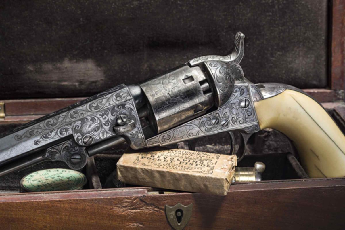 A factory-engraved cased Colt Model 1849 Pocket in it's case.