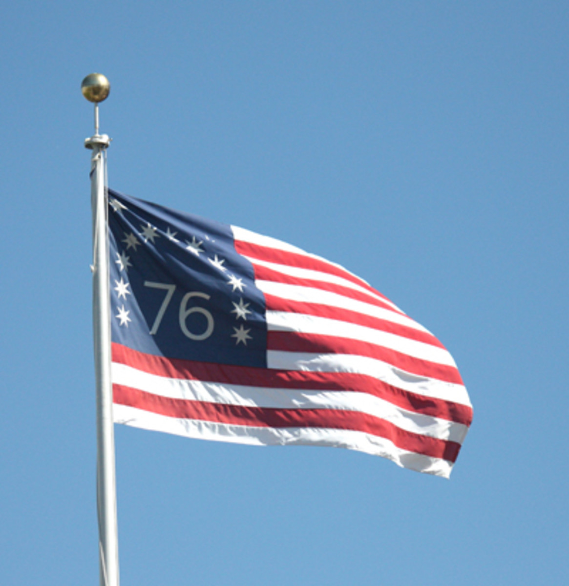 """Dad proudly flew a """"Bennington"""" style flag in front of our store during the 1970s. he Bennington version is easily identified by a large '76' in the canton, recalling the year 1776, when the Declaration of Independence was signed. Another distinctive feature of the Bennington flag is the arrangement of the 13 stripes, with white being outermost (rather than red being outermost as in the current flag). Also, its stars have seven points each (instead of the current five) and the blue canton is taller than on other flags, spanning nine instead of seven of the thirteen stripes. The example shown here was photographed flying over San Francisco City Hall."""
